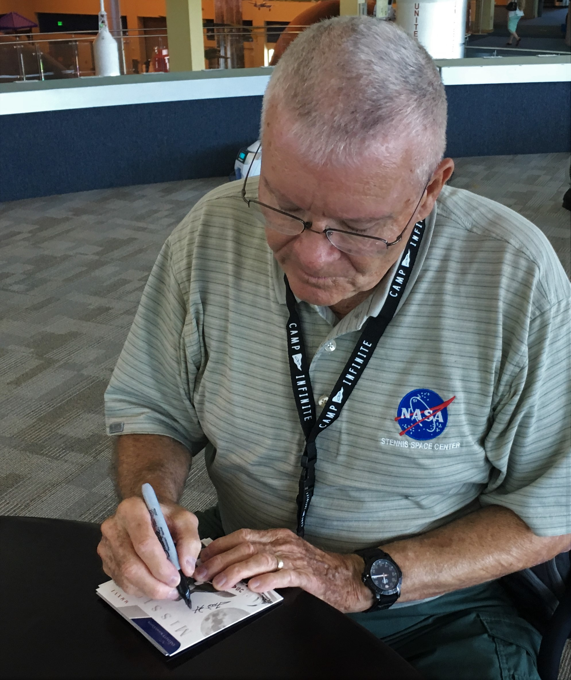 Fred Haise signing Apollo 19 commemorative patch